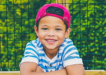 Young boy with backward baseball cap smiling