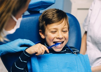 A child brushing his teeth in the dental chair